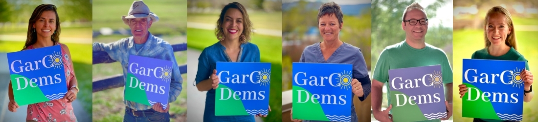 People each holding Garfield County Democrats sign